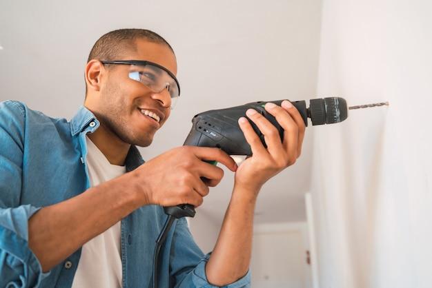 電気ドリルと壁に穴を開ける若いラテン系男性の肖像画。インテリアデザインと住宅リフォームのコンセプト。 Premium写真