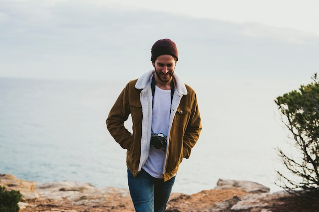 屋外カメラを運ぶ若い男の肖像 Premium写真