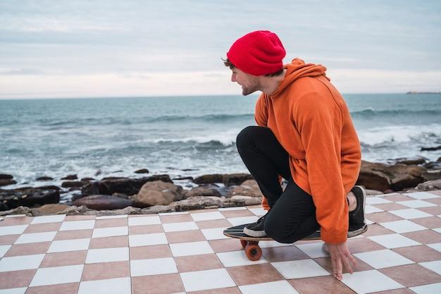 Портрет молодого человека, развлекающегося со своим скейтбордом и практикующего свои трюки с морем в космосе. Бесплатные Фотографии