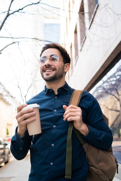 通りで屋外を歩きながらコーヒーを持っている若い男の肖像画。アーバンとライフスタイルのコンセプト。 無料写真