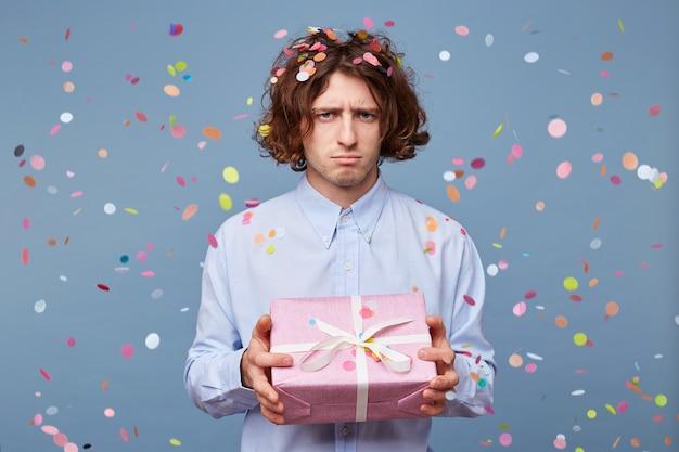 현재 장식 된 분홍색 상자를 들고 젊은 남자의 초상화 슬픈 보인다 무료 사진
