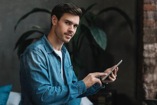 デジタルタブレットを手にしてカメラを見ている若い男の肖像画 無料写真
