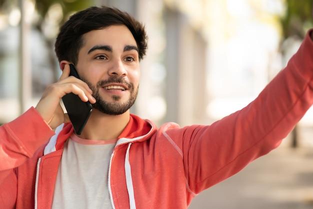 通りで屋外に立っている間、電話で話し、タクシーを呼ぶために手を上げる若い男の肖像画。アーバンコンセプト。 無料写真