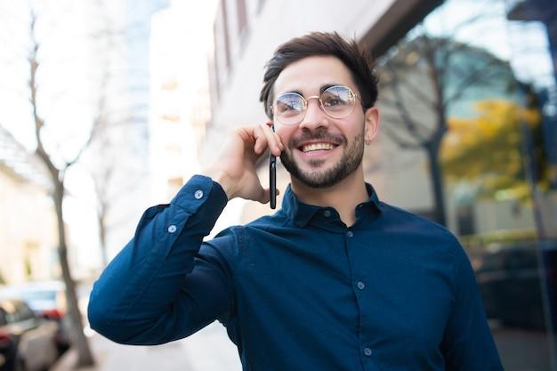 通りを屋外で歩きながら電話で話している若い男の肖像画。アーバンコンセプト。 無料写真