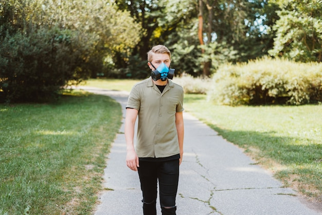 Портрет молодого человека, идущего в парке и носящего респиратор, будь в безопасности covid19. Premium Фотографии