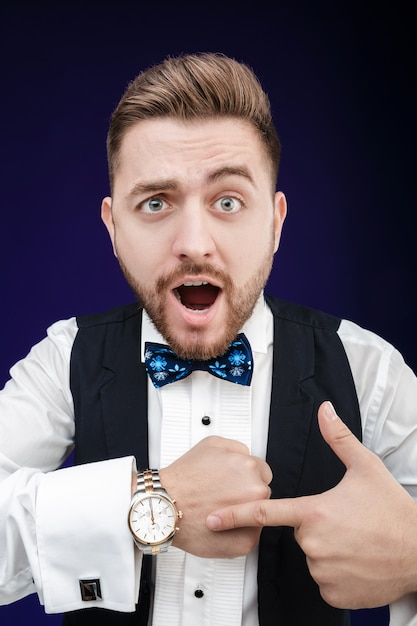 Портрет молодого человека с бородой показывает часы Premium Фотографии