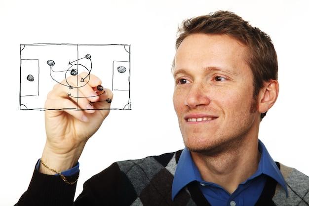 Портрет молодого человека, пишущего на стеклянной доске, изолированной на белом Premium Фотографии