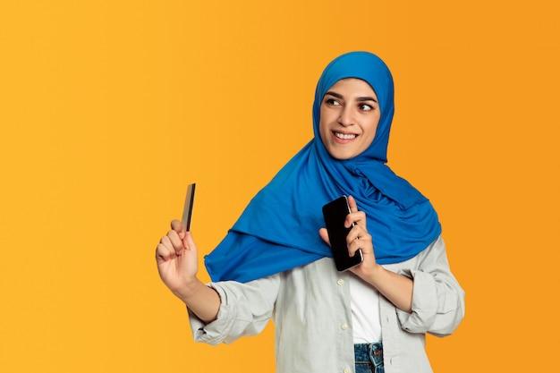 Портрет молодой мусульманской женщины, изолированной на желтом фоне студии Бесплатные Фотографии