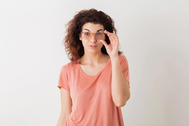 Портрет молодой естественной красивой женщины с вьющейся прической в розовой рубашке, позирует в очках, изолированные, удивленное выражение лица Бесплатные Фотографии