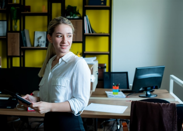 オフィスで立っている顔の作業に笑顔でよそ見タブレットを保持している若いサラリーマン女性の肖像画 無料写真