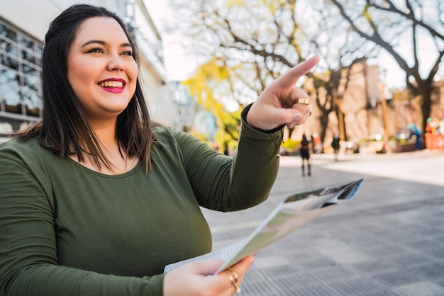 地図を押しながら路上で屋外で道順を探している若いプラスサイズの女性の肖像画。旅行の概念。 無料写真
