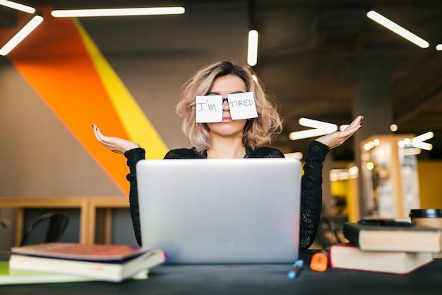 共同作業のオフィス、変な顔の表情、困惑した感情、問題でラップトップに取り組んでいる黒いシャツのテーブルに座ってメガネに紙のステッカーを持つ若いかなり疲れた女性の肖像画 無料写真