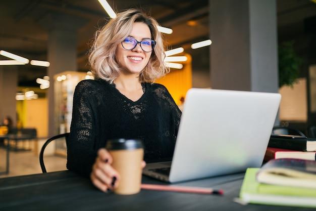 Портрет молодой красивой женщины, сидящей за столом в черной рубашке, работающей на ноутбуке в коворкинге Бесплатные Фотографии
