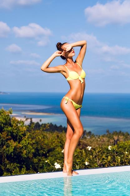 Портрет молодой сексуальной женщины с идеальным загорелым стройным телом, носить бикини и солнцезащитные очки, наслаждаясь в отпуске. красивый вид с дурака на острове Бесплатные Фотографии
