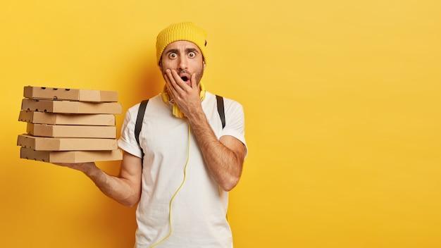 若いショックを受けた男性の配達労働者の肖像画は、ピザの箱のスタックを保持し、カジュアルな服を着て、開いた口を覆い、黄色の壁に立っています 無料写真
