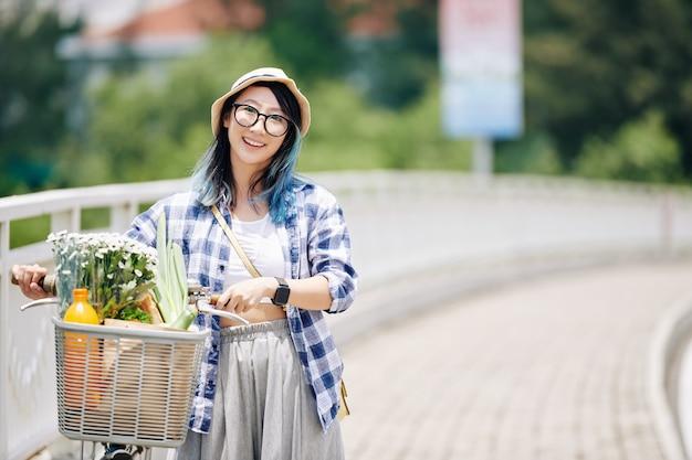 自転車で道を歩いている若い笑顔のアジアの女性の肖像画。バスケットは食料品や花でいっぱいです Premium写真