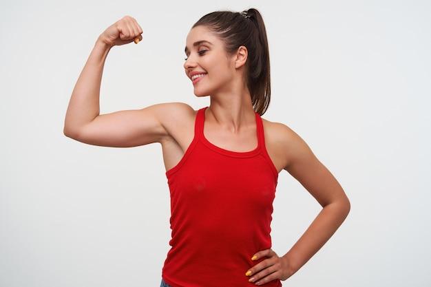 赤いtシャツを着た若い笑顔のかわいいブルネットの女性の肖像画は、becepsと優れたフィットネスフォームを示しています。白い背景の上に立っています。 無料写真