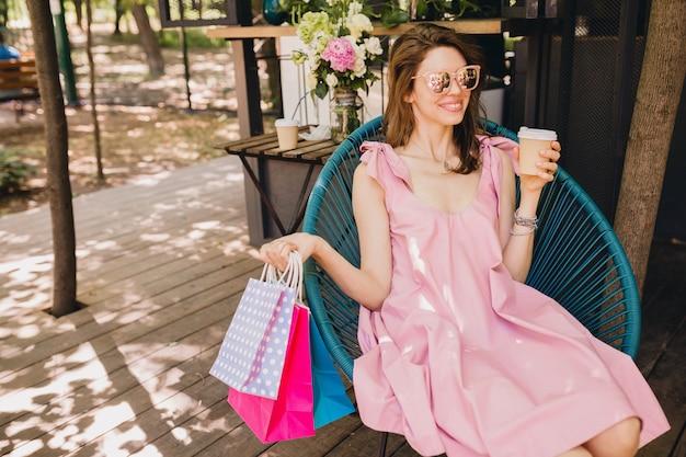 쇼핑백 커피를 마시는 카페에 앉아 젊은 미소 행복 매력적인 여자의 초상화, 여름 패션 복장, 핑크면 드레스, 최신 유행의 의류 무료 사진