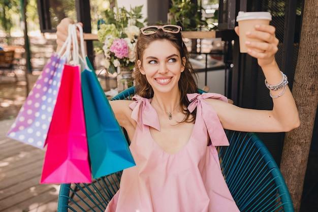 커피, 여름 패션 복장, 힙 스터 스타일, 핑크면 드레스, 트렌디 한 의류를 마시는 쇼핑백과 함께 카페에 앉아 흥분된 얼굴 표정으로 젊은 웃는 행복 예쁜 여자의 초상화 무료 사진