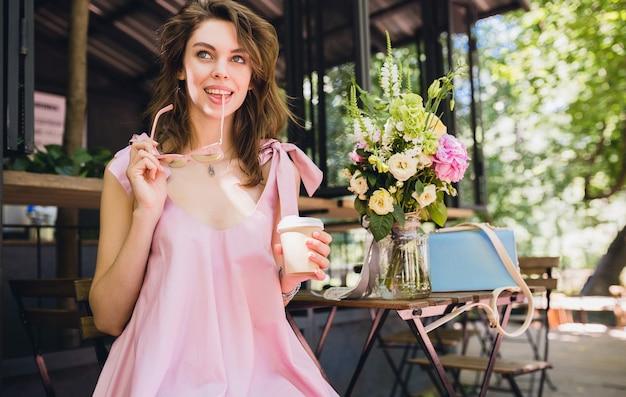 Портрет молодой улыбающейся счастливой красивой женщины с сидящим в кафе, пьющим кофе, летним модным нарядом, хипстерским стилем, розовым хлопковым платьем, модными аксессуарами для одежды Бесплатные Фотографии