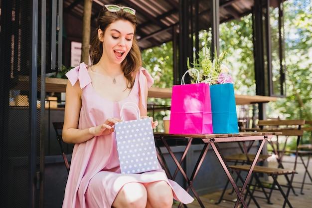 쇼핑백, 여름 패션 복장, 핑크색 면화 드레스, 최신 유행의 의류와 카페에 앉아 놀란 얼굴 표정으로 젊은 미소 행복 예쁜 여자의 초상화 무료 사진