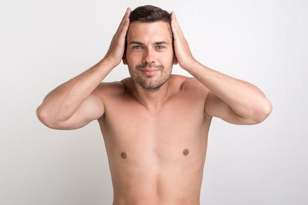 白い背景に対して立っているカメラを見て彼の髪に触れる若い笑みを浮かべて男の肖像 無料写真