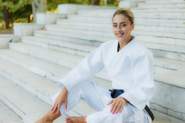 Портрет молодой усмехаясь женщины в белом кимоно с черным поясом. спортивная женщина сидит на лестнице на открытом воздухе. боевые искусства Premium Фотографии