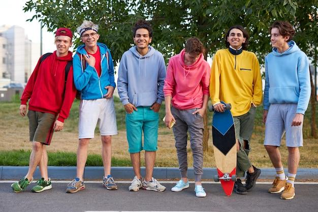 スケートボードを持つティーンエイジャーの若いスポーツチームの肖像画 Premium写真