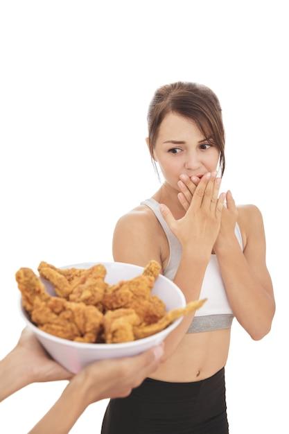 Портрет молодой спортивной женщины, сопротивляющейся искушению жареной курицы Premium Фотографии