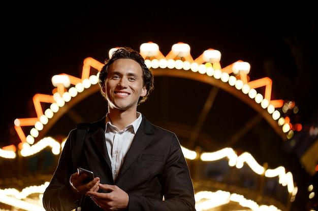 Портрет молодого успешного бизнесмена над парком развлечений ночи. неглубоко фо Бесплатные Фотографии