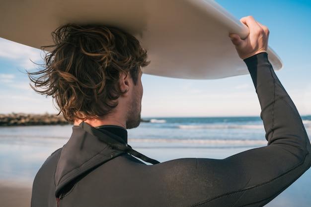 Портрет молодого серфера на пляже, подняв доску для серфинга и одетого в черный костюм для серфинга. концепция спорта и водных видов спорта. Бесплатные Фотографии