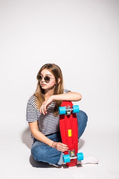 白い壁の上に立っている間スケートボードでポーズのサングラスで若い十代の少女の肖像画 無料写真