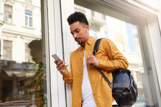 Портрет молодого мыслящего темнокожего парня в желтой рубашке, идущего по улице, держит телефон, болтает с подругой, смотрит сосредоточенно. Бесплатные Фотографии