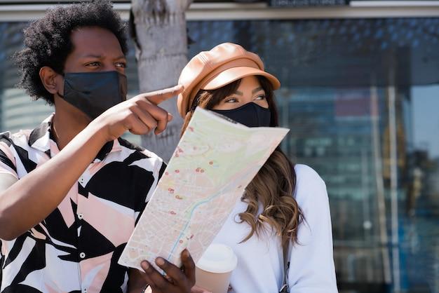 Портрет молодой туристической пары, использующей защитную маску и смотрящей на карту, ища направления на открытом воздухе. концепция туризма. новая концепция нормального образа жизни. Premium Фотографии
