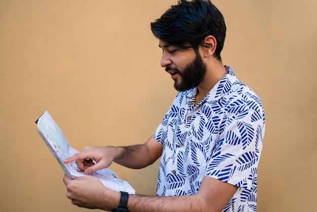 夏の服を着て、黄色に対する方向を探しているマップを保持している若い観光客の男の肖像。 無料写真