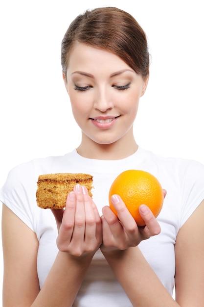 ケーキとオレンジのどちらかを選択する若い女性の肖像画 無料写真