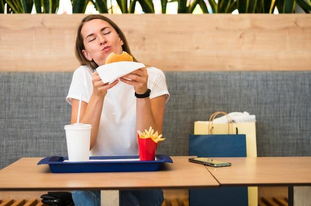 Портрет молодой женщины, едящей фаст-фуд Бесплатные Фотографии