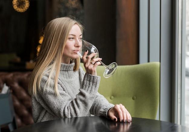 ワインのグラスを楽しむ若い女性の肖像画 無料写真