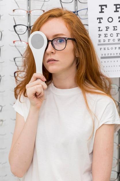 Портрет молодой женщины, держащей оптику окклюдера перед ее глазом Бесплатные Фотографии