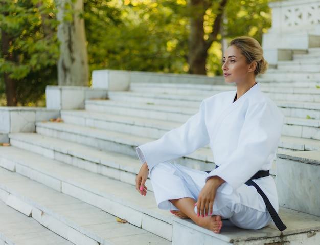 Портрет молодой женщины в белом кимоно с черным поясом. спортивная женщина сидит на лестнице на открытом воздухе. боевые искусства Premium Фотографии