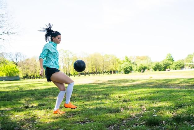 Портрет молодой женщины, практикующей футбол и выполняющей трюки с футбольным мячом Бесплатные Фотографии