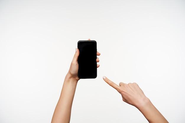 Портрет руки молодой женщины, которые поднимаются, держа в нем смартфон и показывая на экране указательным пальцем, изолированным на белом Бесплатные Фотографии
