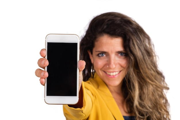 Портрет молодой женщины показывая пустой экран смартфона и смотря камеру на белой предпосылке. Premium Фотографии