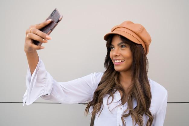 屋外に立っている間彼女のmophile電話でselfiesを取る若い女性の肖像画 無料写真