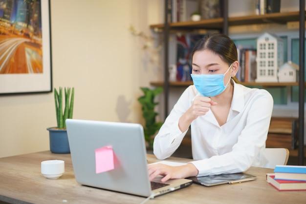 感染症を防ぐために顔の保護マスクを身に着けているカフェでラップトップを使用して若い女性の肖像画 Premium写真