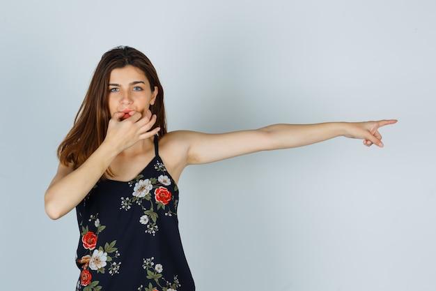 横を指して、指で口笛を吹く若い女性の肖像画 無料写真
