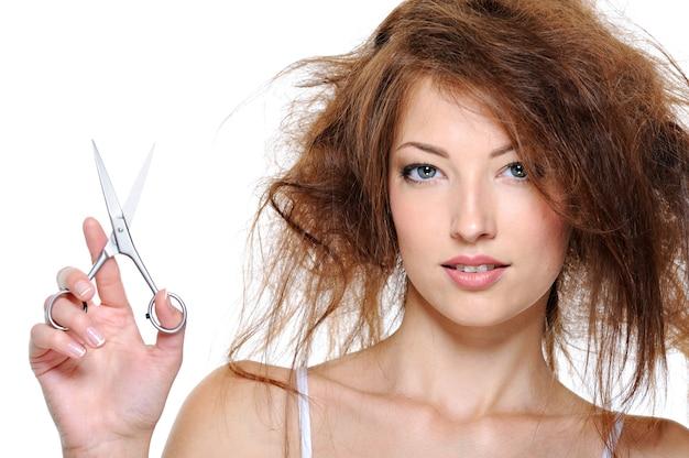 머리를 뒤로 빗질하고 가위를 가진 젊은 여자의 초상화 무료 사진