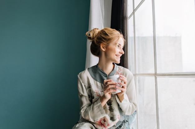 Портрет молодой женщины со светлыми волосами, пить кофе или чай рядом с большим окном, улыбаясь, наслаждаясь счастливым утром дома. бирюзовая стена. ношение шелковой пижамы в цветах. Бесплатные Фотографии