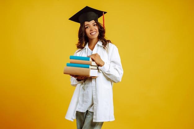 Портрет молодой женщины с книгами, позирующими на желтом. Premium Фотографии