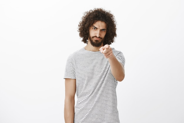 Portrait of offended outraged handsome hispanic guy with beard and afro haircut, pointing with blame at front, frowning and looking from under forehead displeased Free Photo